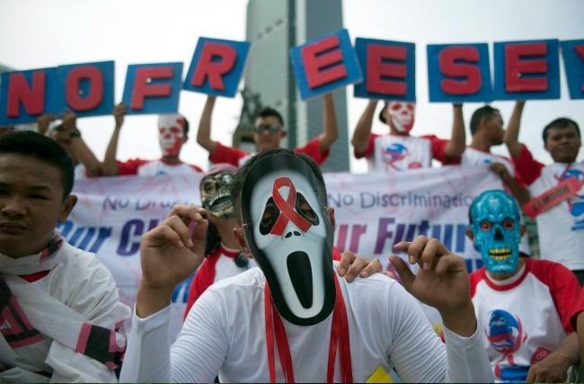 Az AIDS-ellenes kampányt jelképező piros szalaggal díszített halálfejes maszkot visel egy aktivista egy nagygyűlésen Jakartában (Fotó: MTI/EPA/Adi Weda)